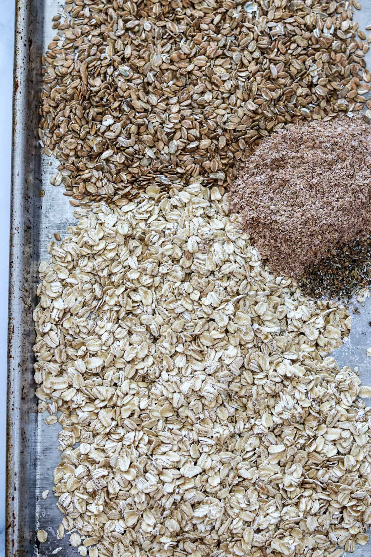 Oats, rye flakes and wheat bran on a sheet pan.