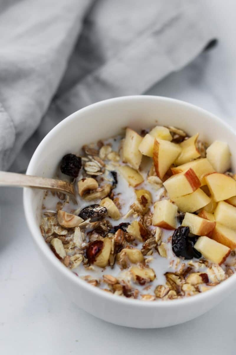 A bowl of muesli with chopped apples next to a napkin.