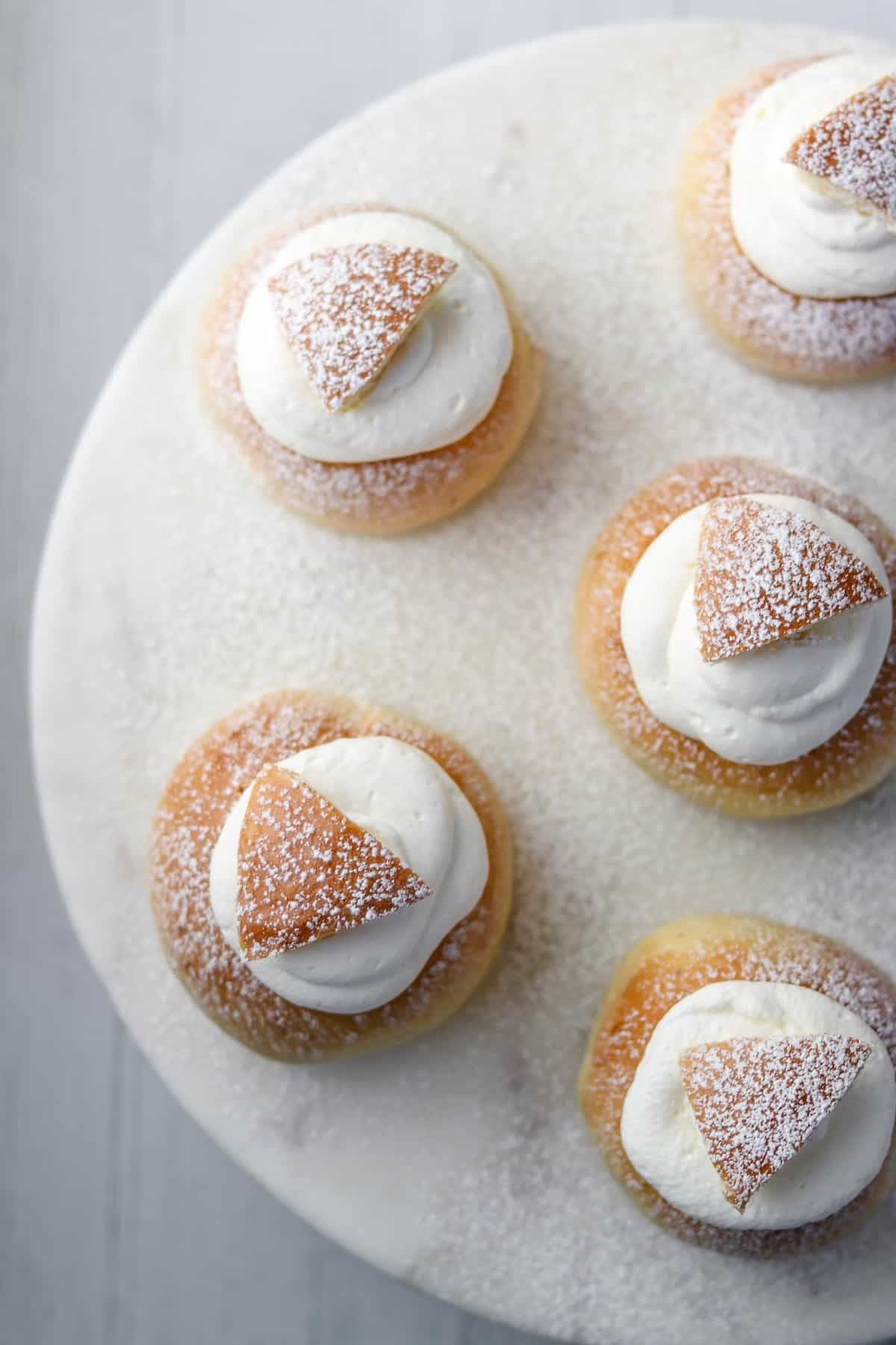 Semlor buns on a marble surface.