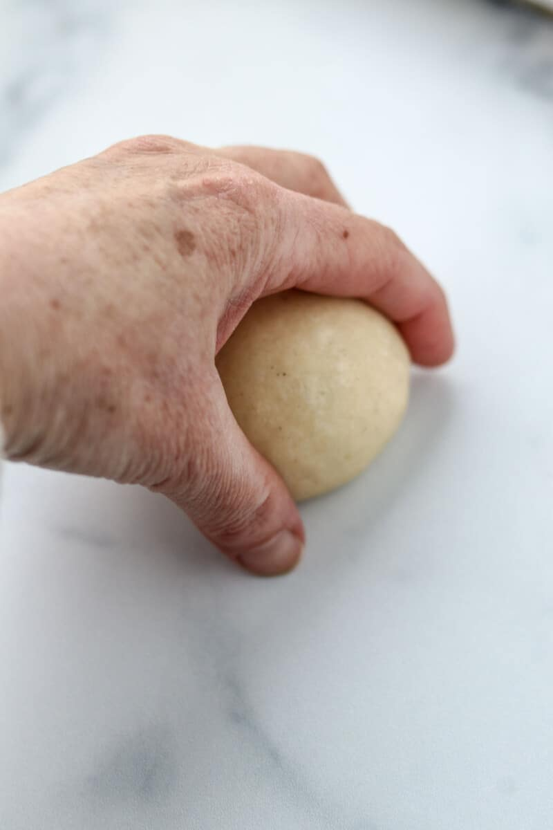 Someone shaping a round bun with their hand on a marble surface.