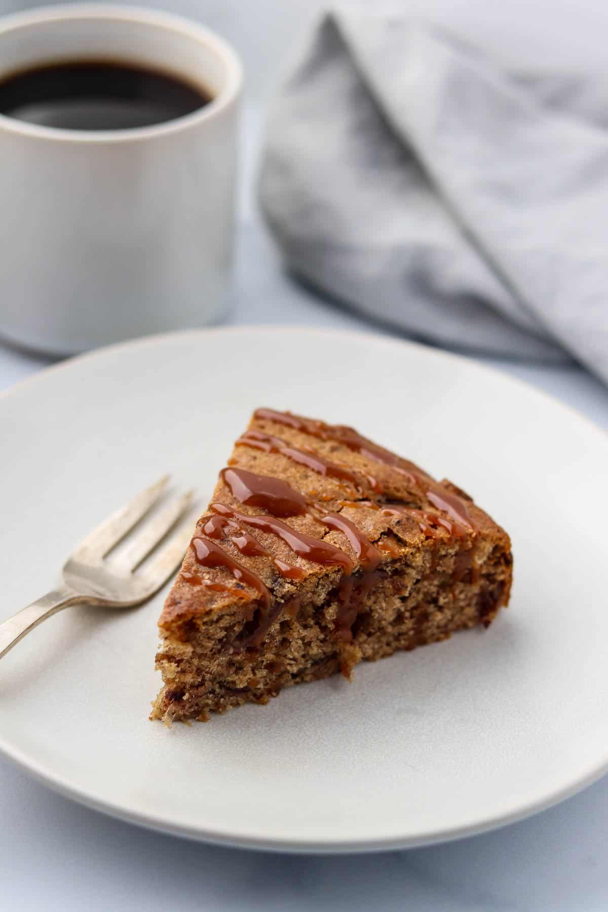 A slice of date cake drizzled with caramel on a plate next to a fork and cup of coffee.