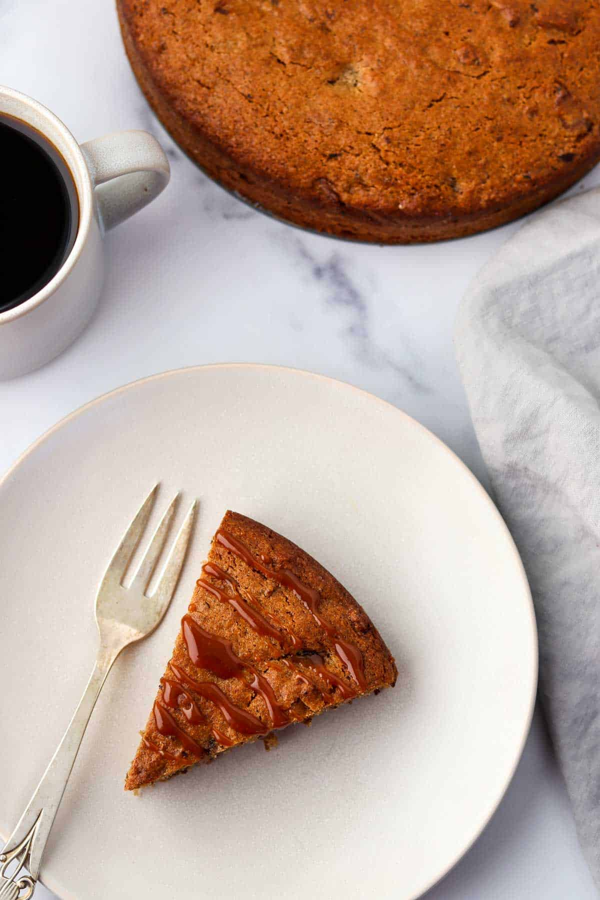 A slice of caramel-drizzled cake on a plate next to a fork and a cup of coffee.