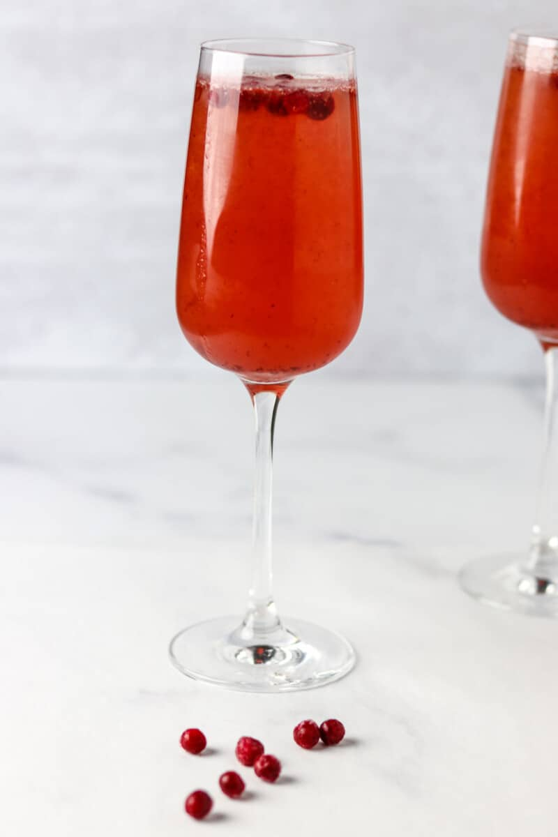 Champagne glass filled with Swedish 75 cocktail next to lingonberries.