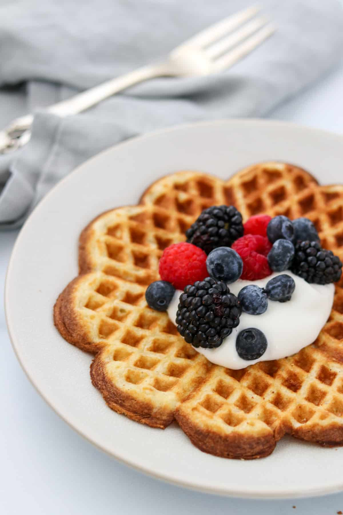 Heart shaped waffle on a plate topped with whipped cream and fruit.