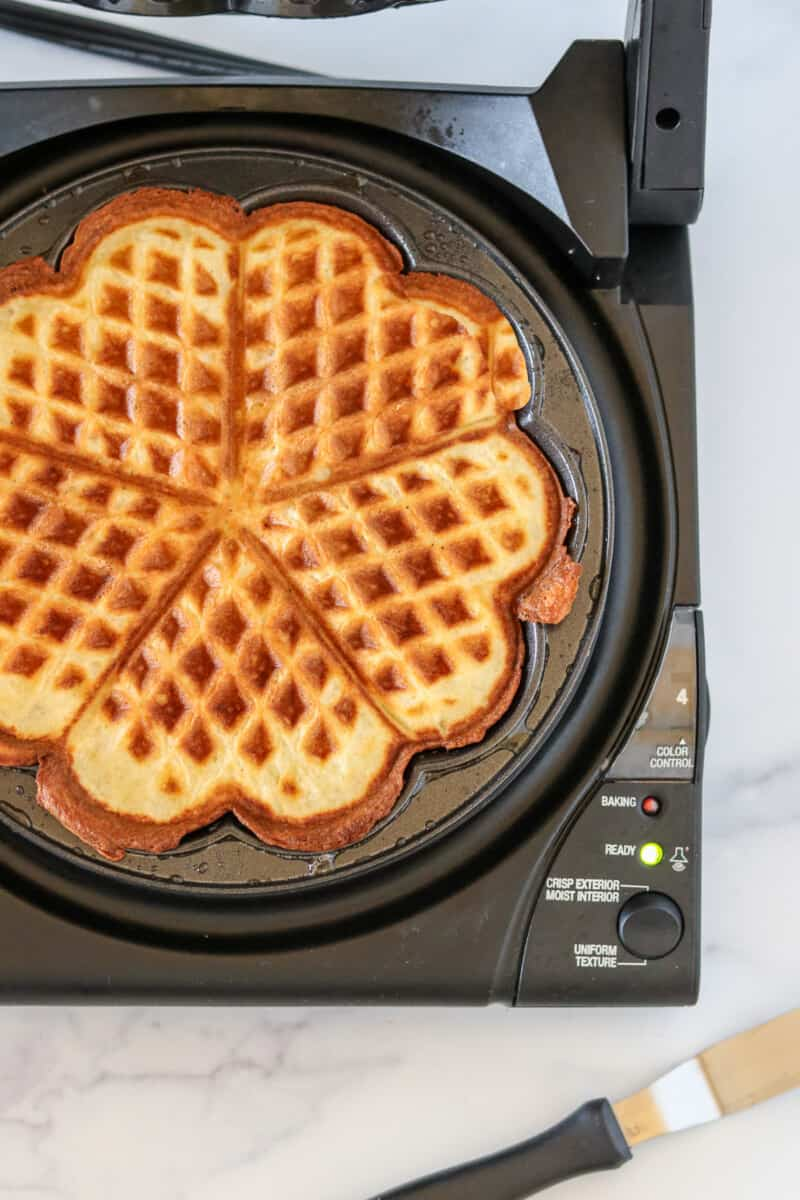 Waffle cooking in a heart shaped waffle iron.