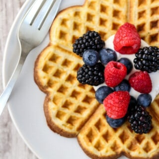 Heart-shaped waffle on a plate topped with whipped cream and fruit.