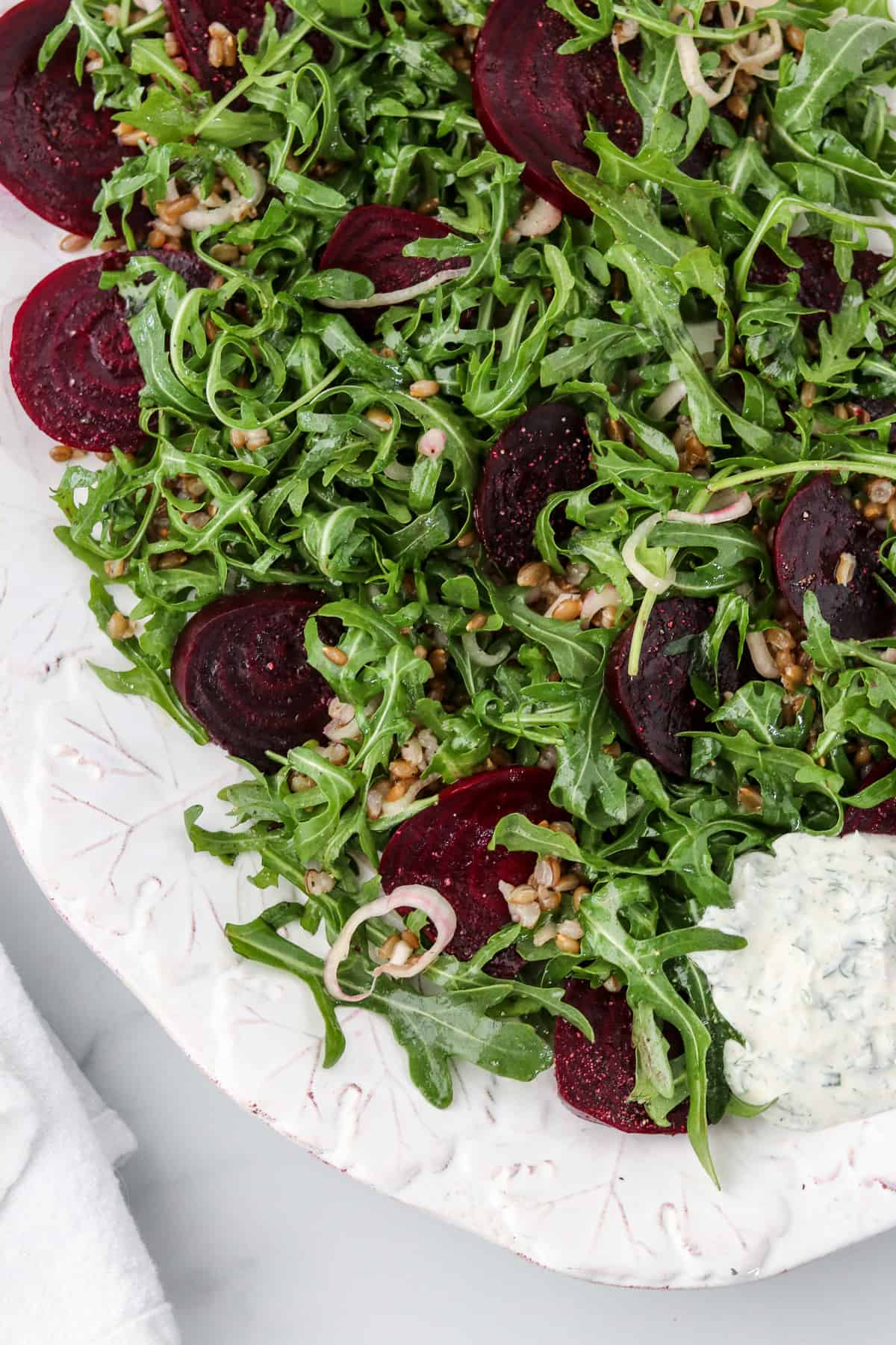 Roasted beet salad on a platter next to a napkin.