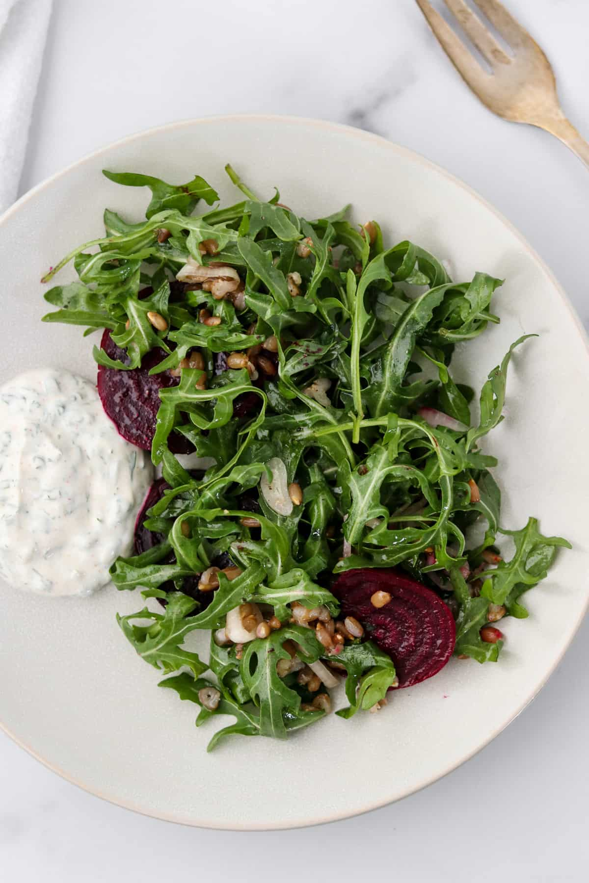 Roasted beet salad on a plate with a creamy sauce.