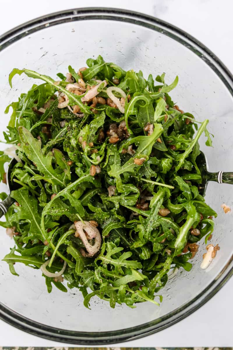 Arugula and shallots tossed in a glass bowl.