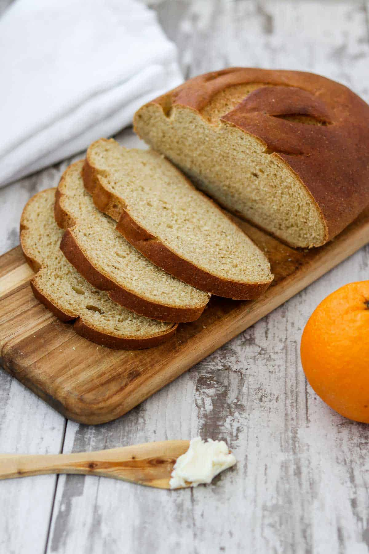 Swedish limpa bread on a cutting board next to butter and an orange.