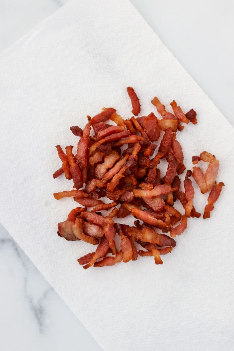 Chopped, cooked bacon on a paper towel.