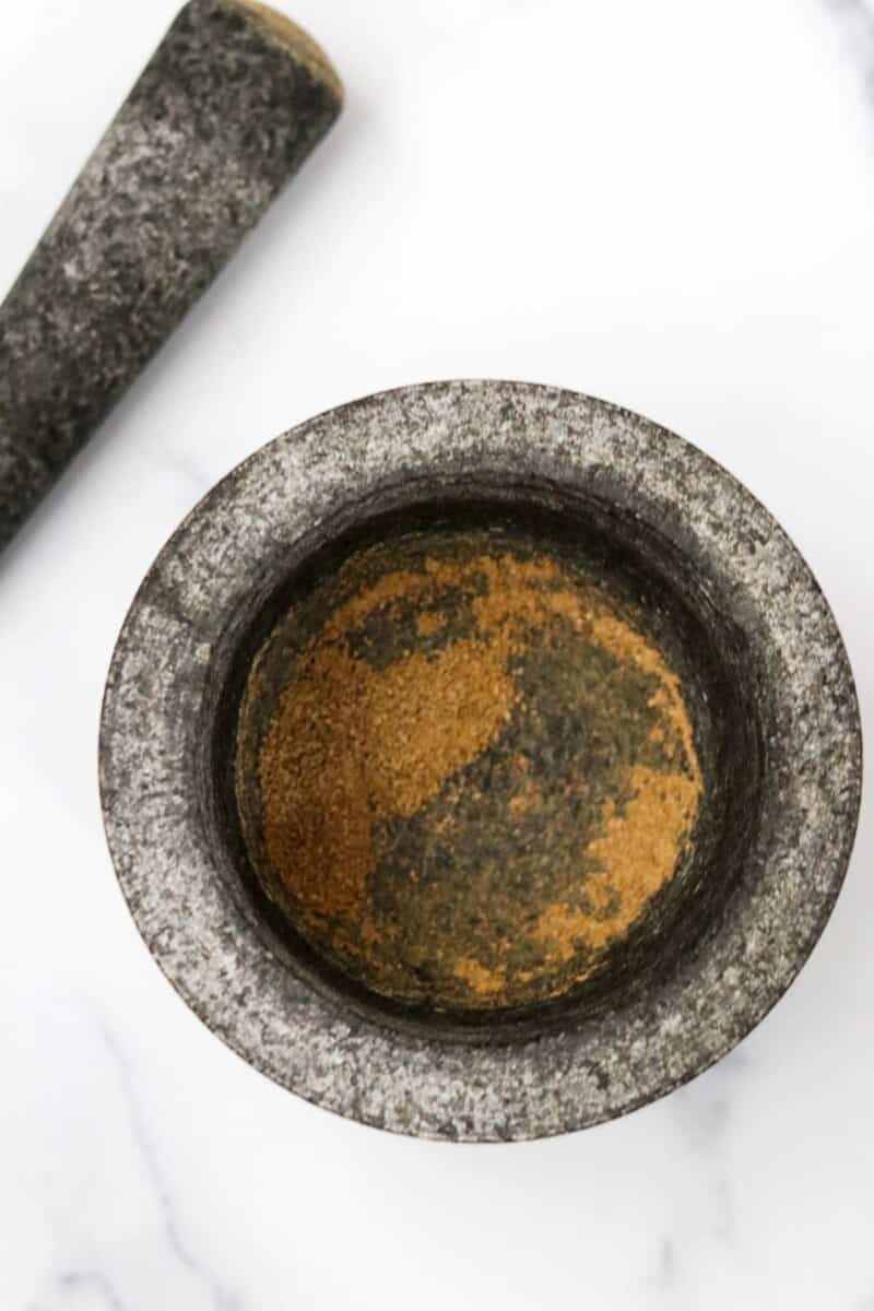 Spices in a mortar next to a pestle.