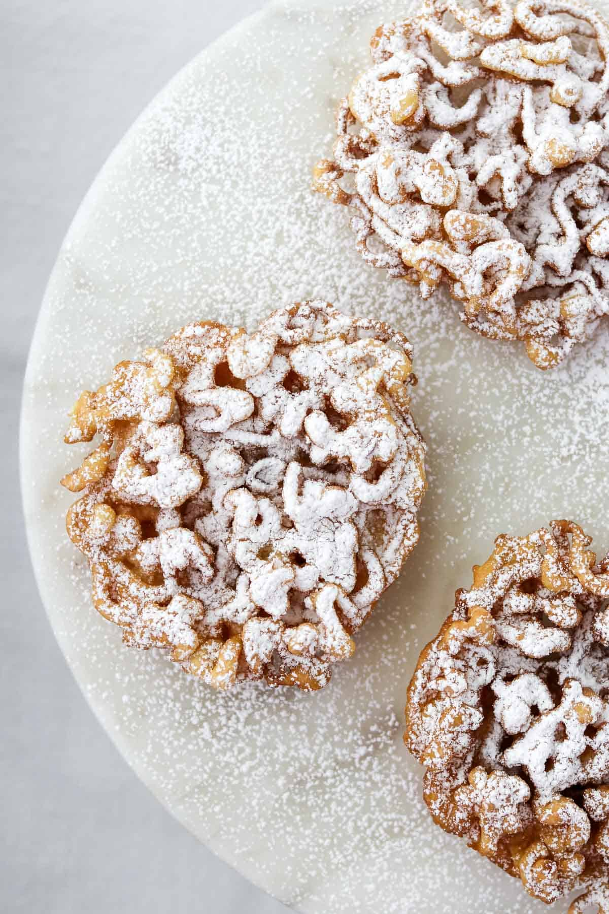 Three funnel cakes dusted in powdered sugar on a marble surface.