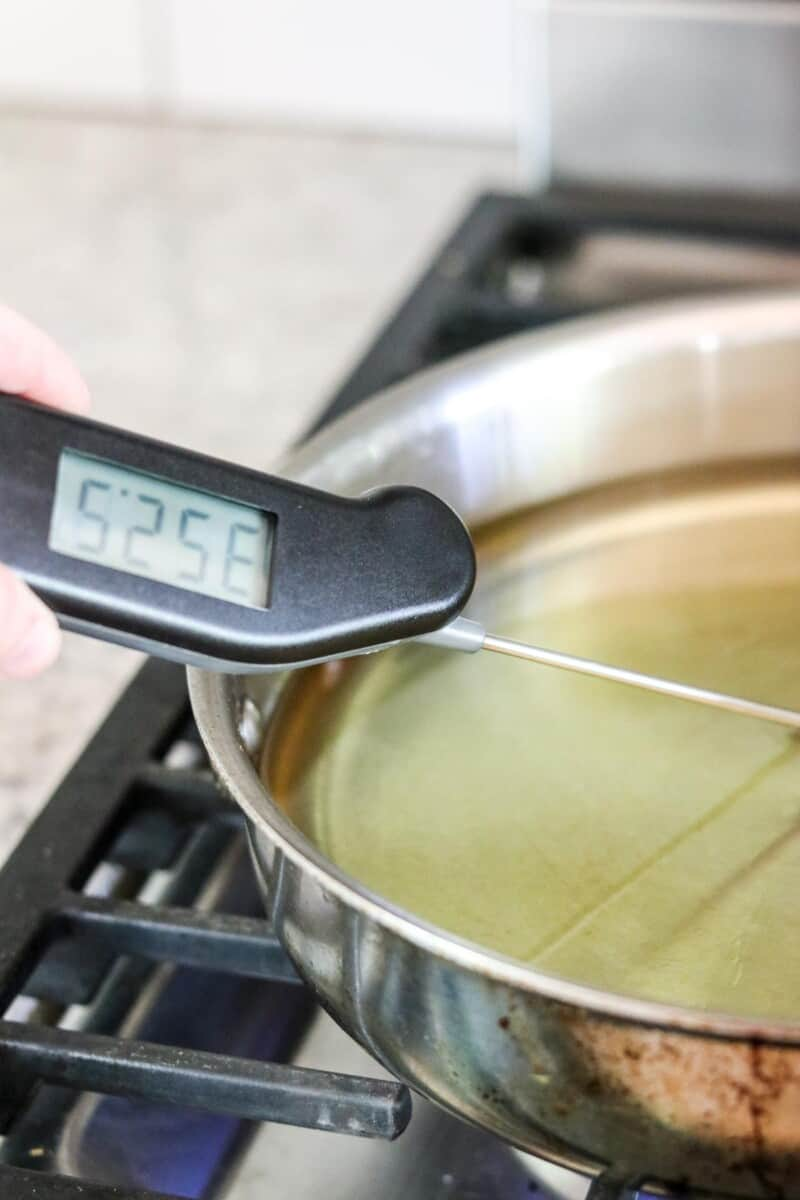 Person taking the temperature of hot oil on the stove..