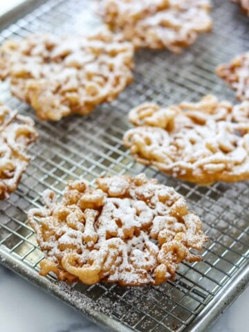 Funnel cakes dusted with powdered sugar on a wire rack.