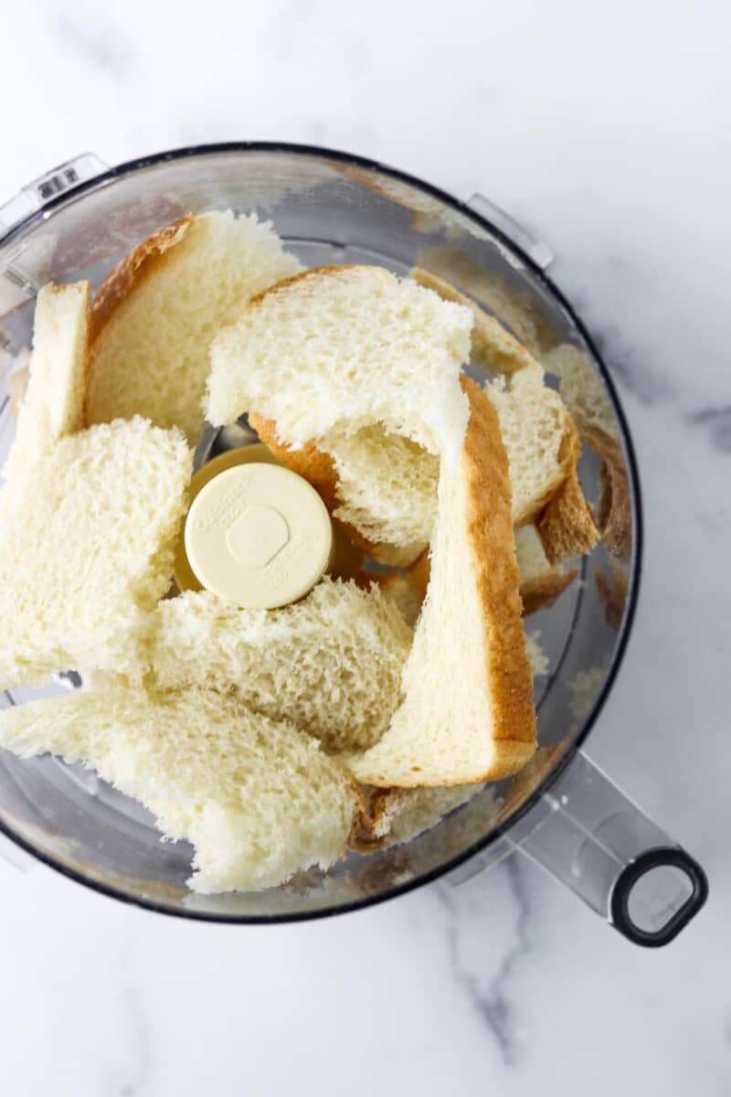 Torn pieces of bread in the work bowl of a food processor.