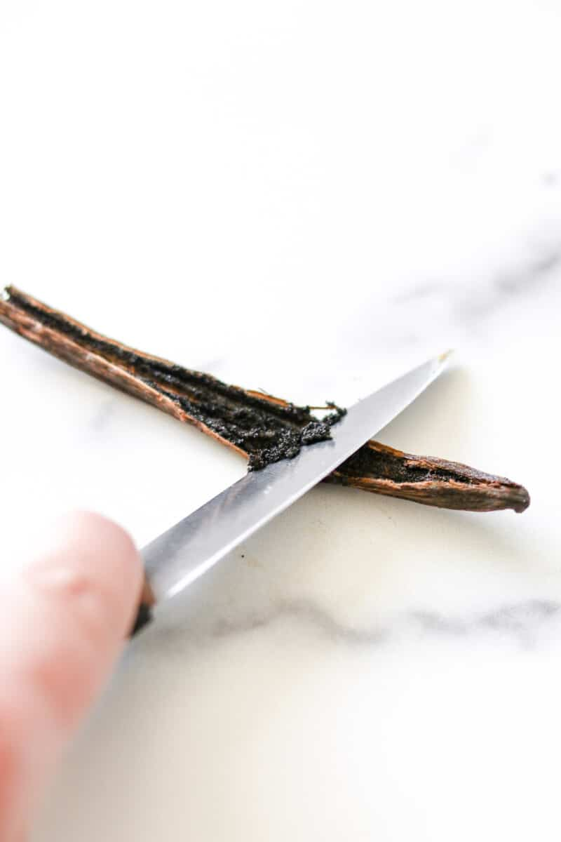 Close up of scraping out a vanilla bean with the back of a knife.