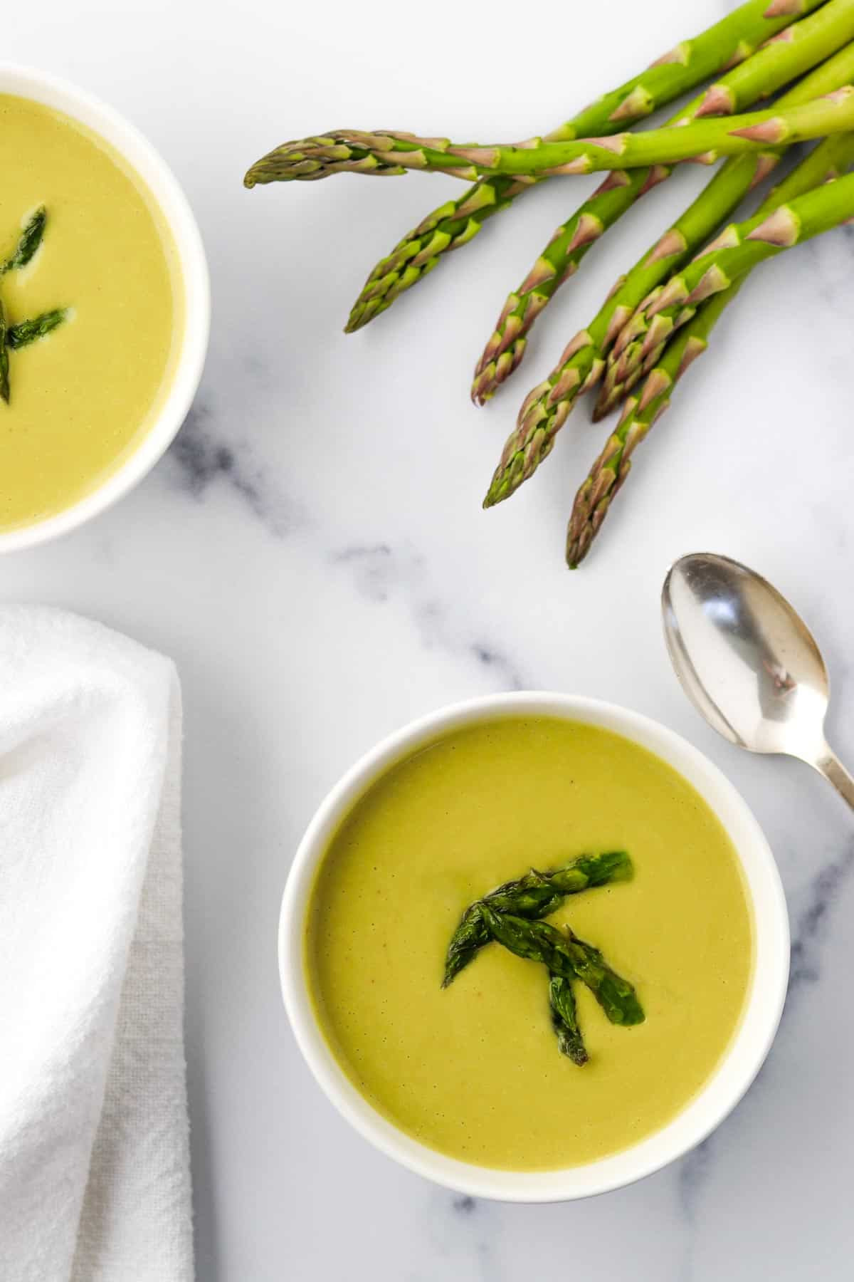 Two bowls of Creamy Asparagus, Leek and Pea Soup next to asparagus spears and a spoon.
