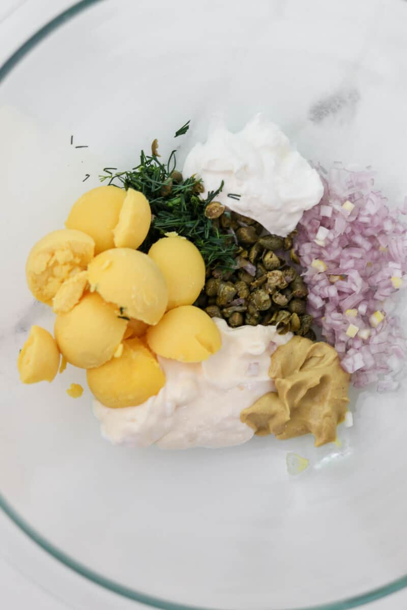 Ingredients for egg salad in a bowl before being mixed.