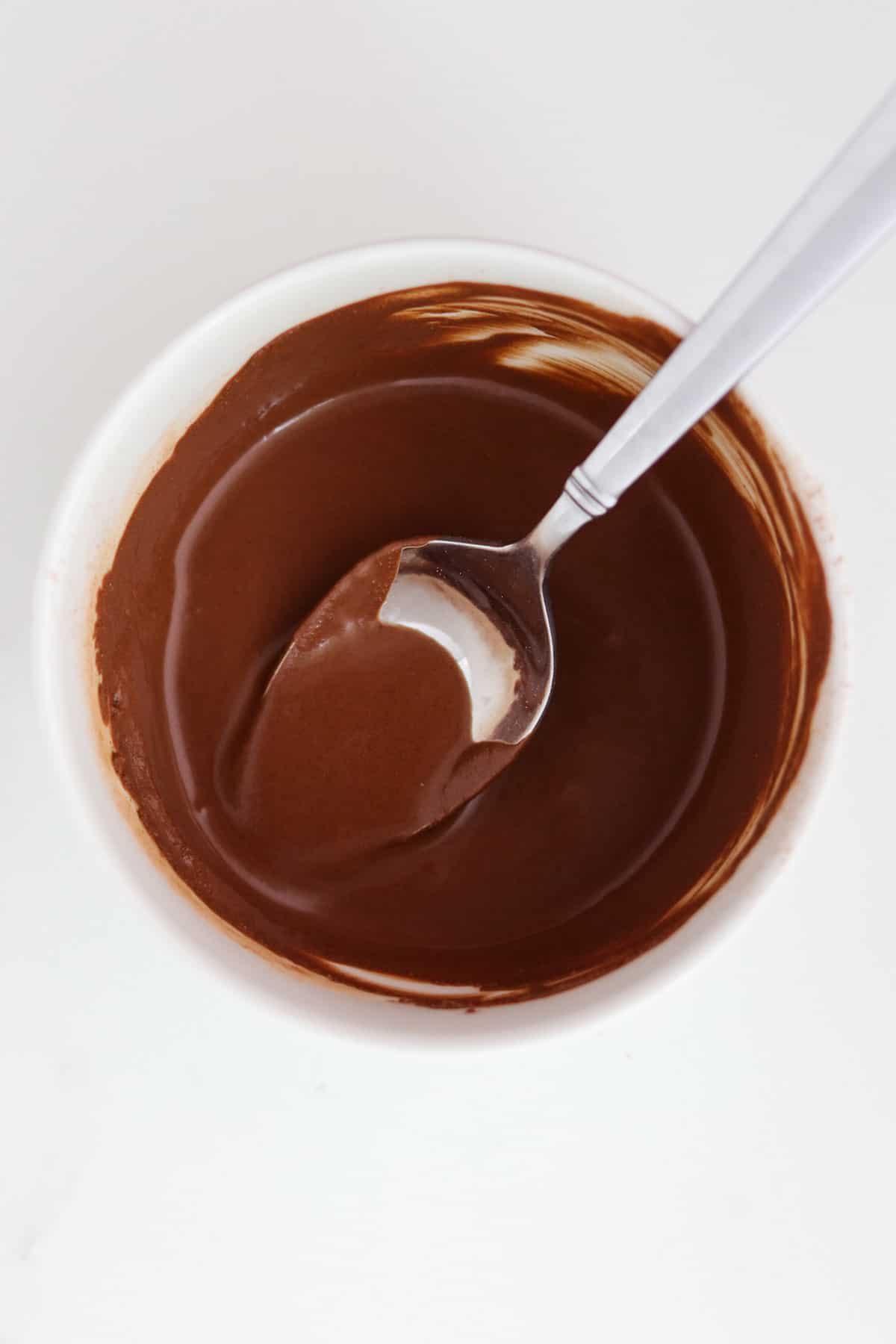 Melted chocolate in a bowl with a spoon.