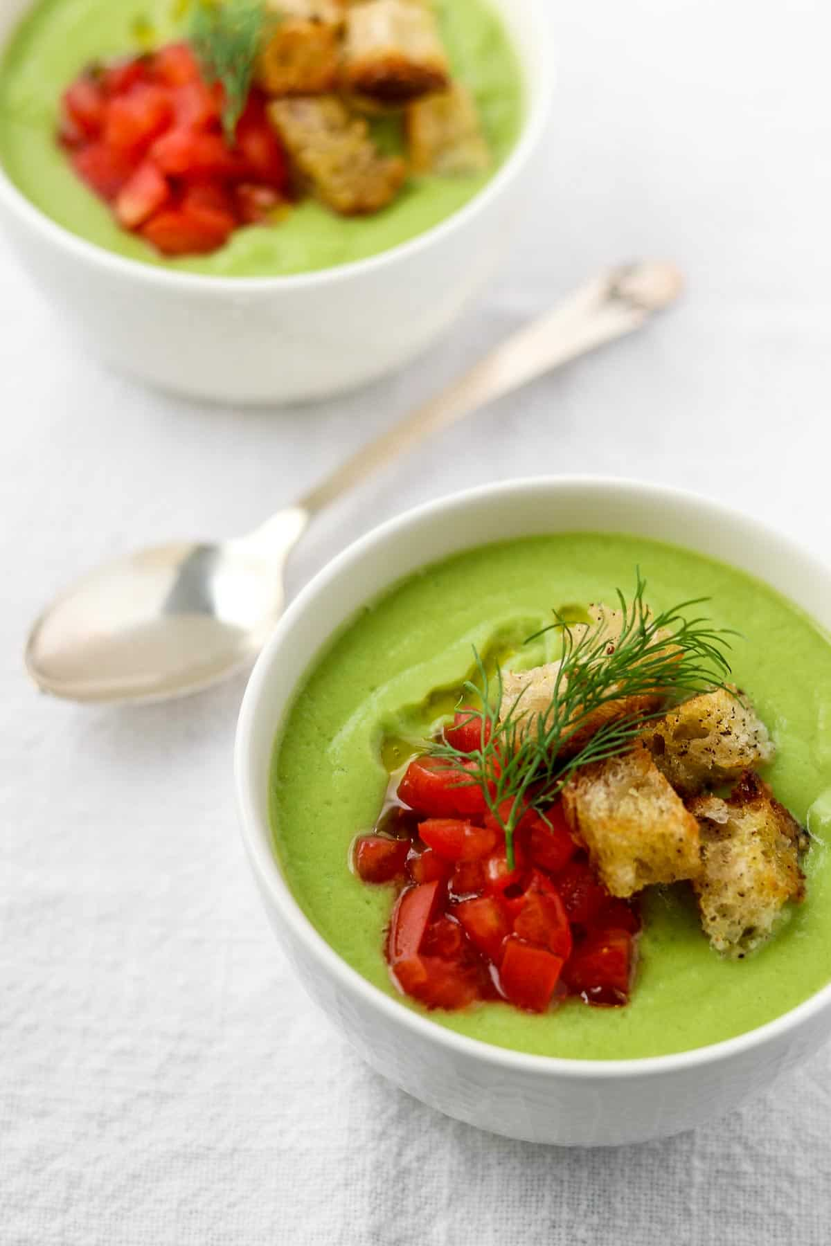 Two bowls of chilled cucumber soup with tomatoes, croutons and dill on top.