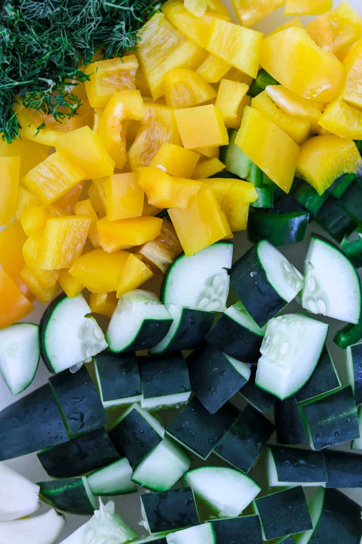 Chopped dill, yellow peppers and cucumbers.