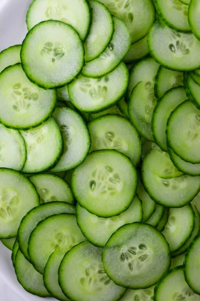 Sliced cucumbers on a white plate.