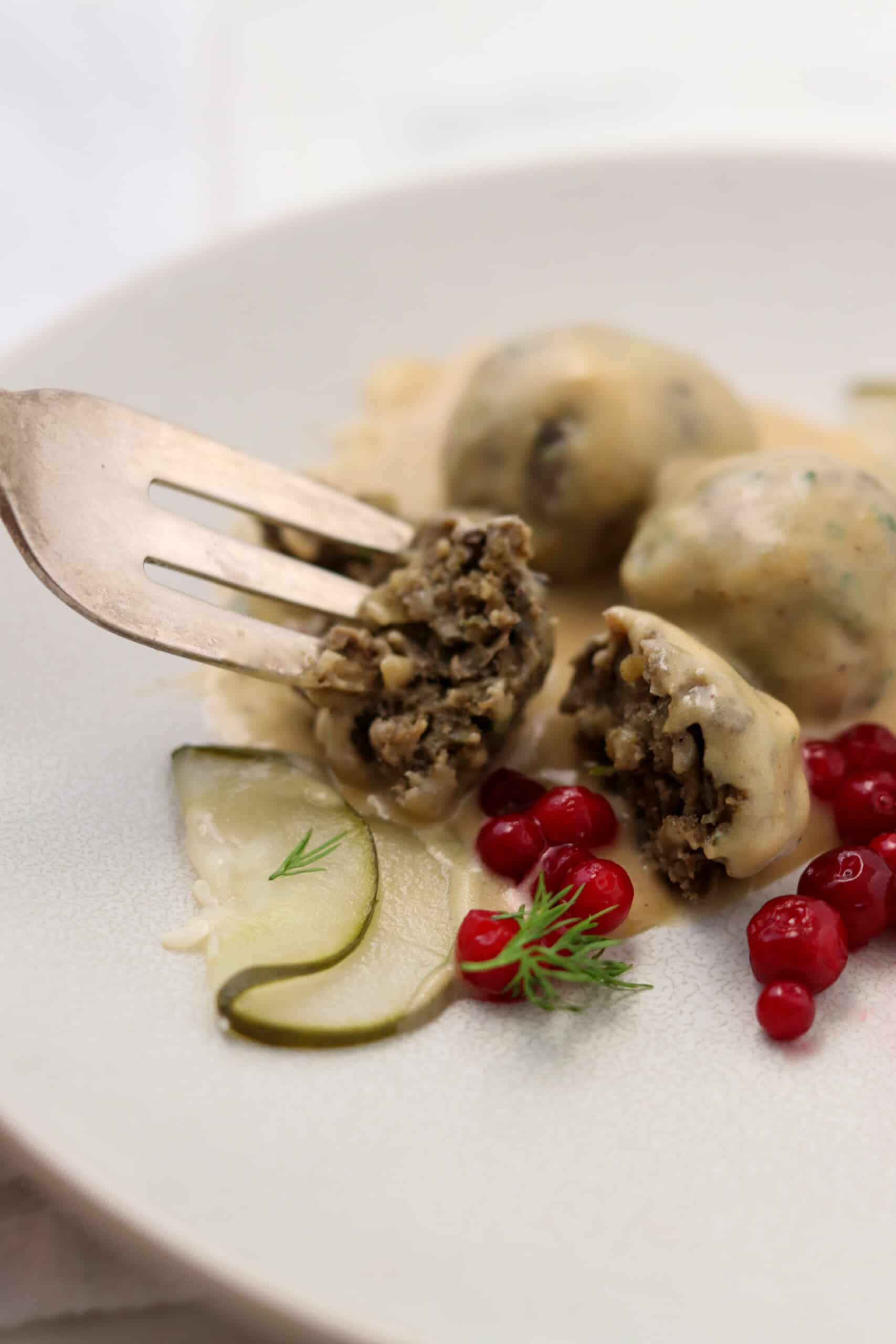Close up of Vegetarian Swedish Meatballs with pickles and lingonberries.