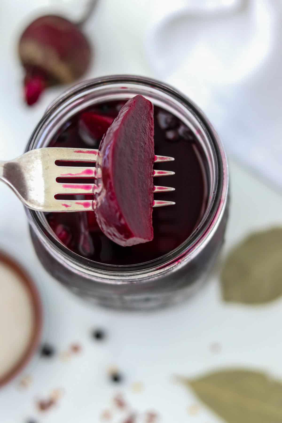 A pickled beet on a fork over a jar.