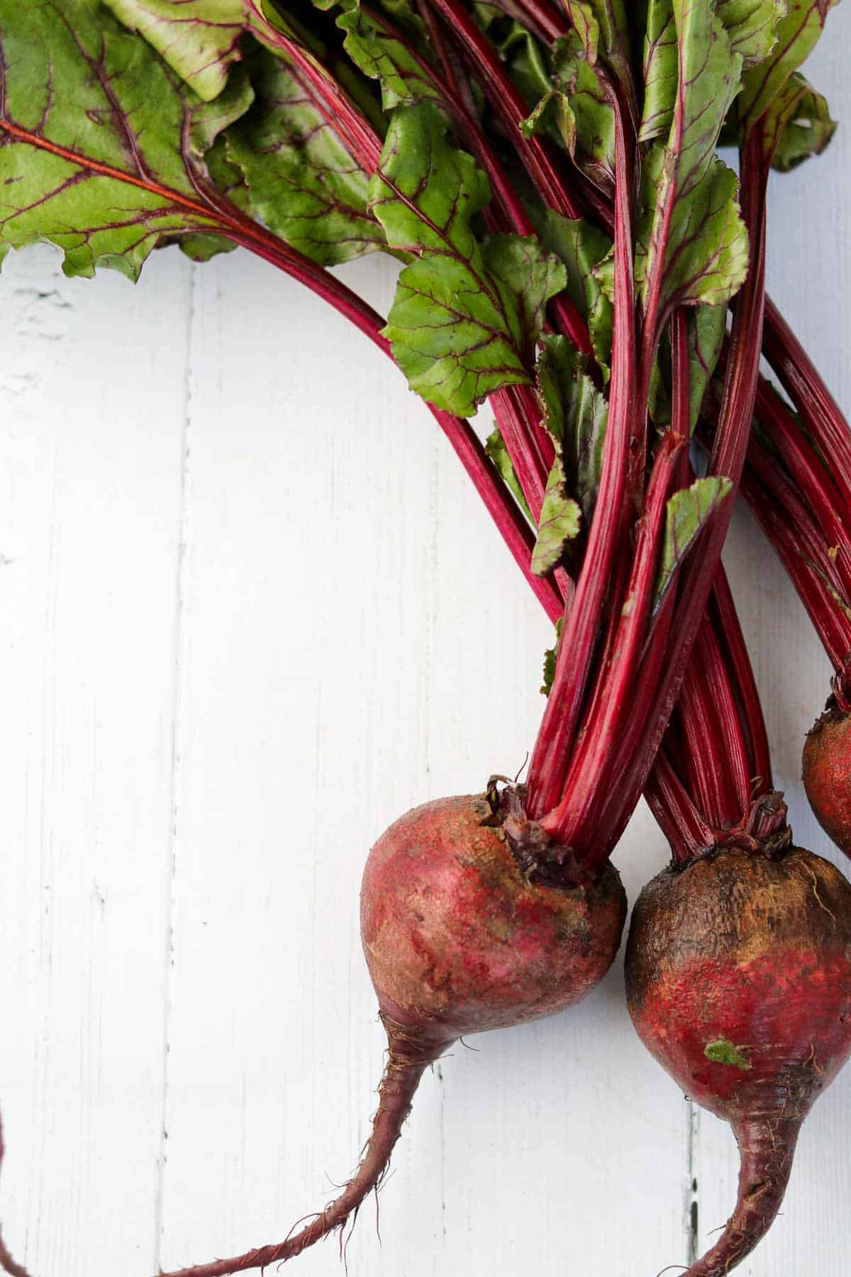 Beets on a white wooden surface.