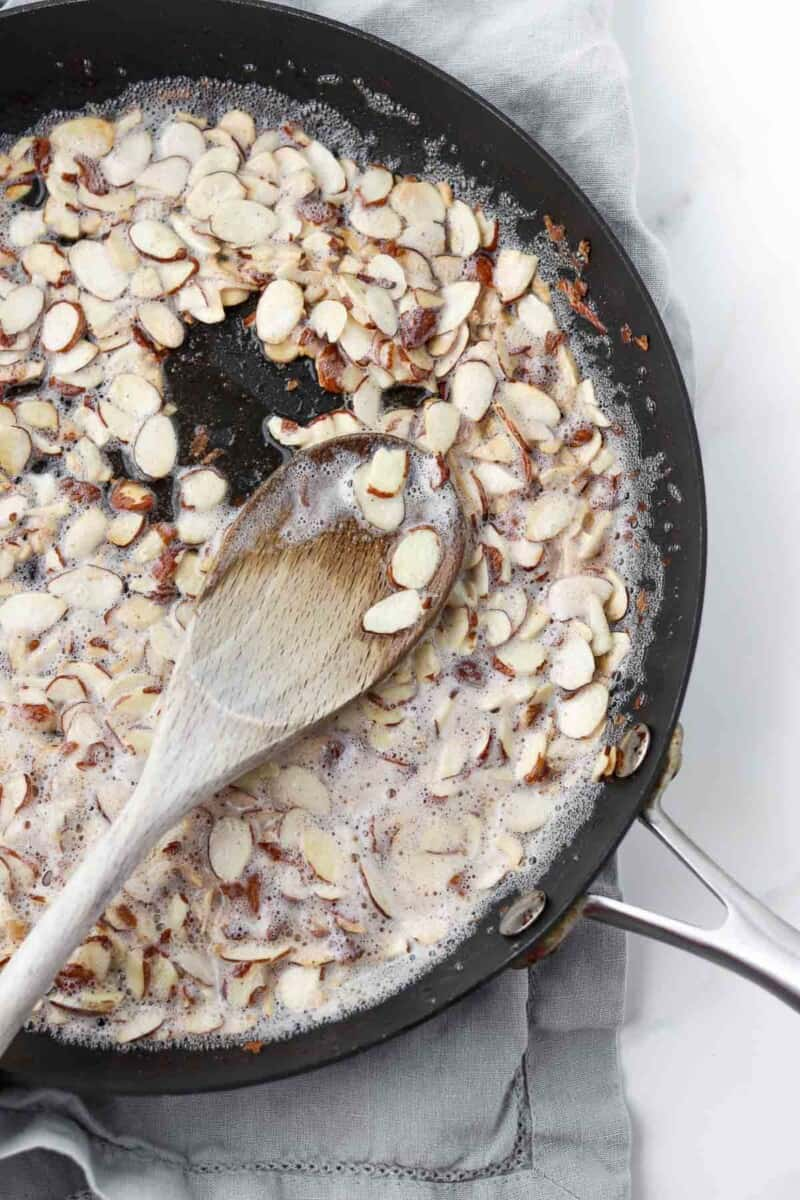 Sliced almonds cooking in butter in a skillet with a wooden spoon.