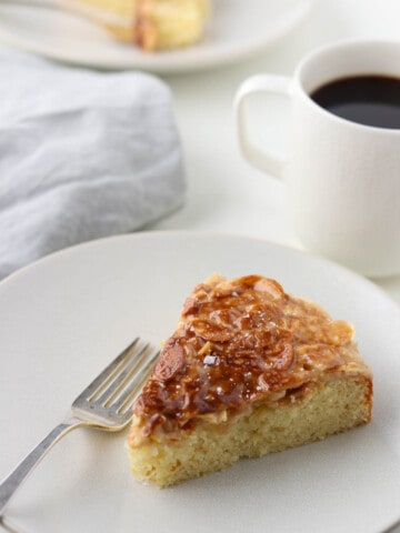 A slice of cake topped with caramelized onions next to a fork and a cup of coffee.