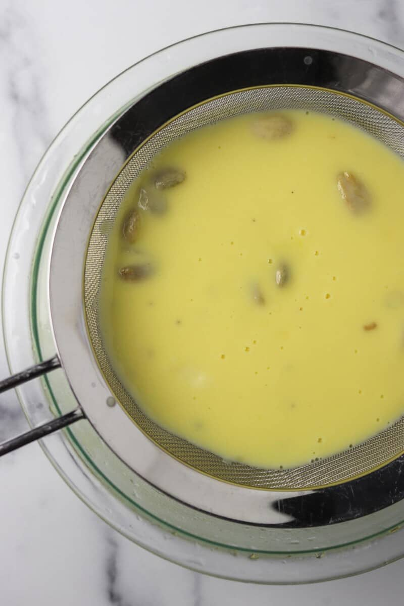 Custard with cardamom pods in a metal strainer.