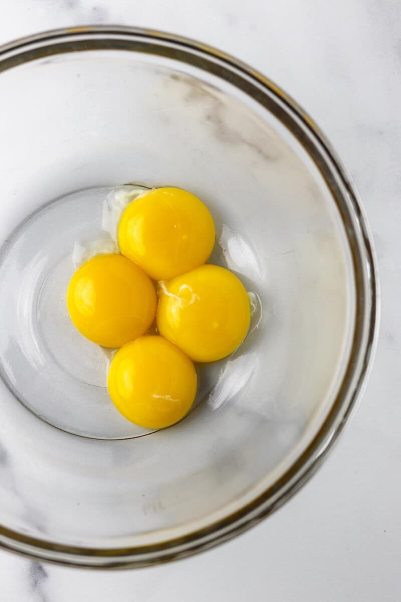 4 egg yolks in a glass bowl.