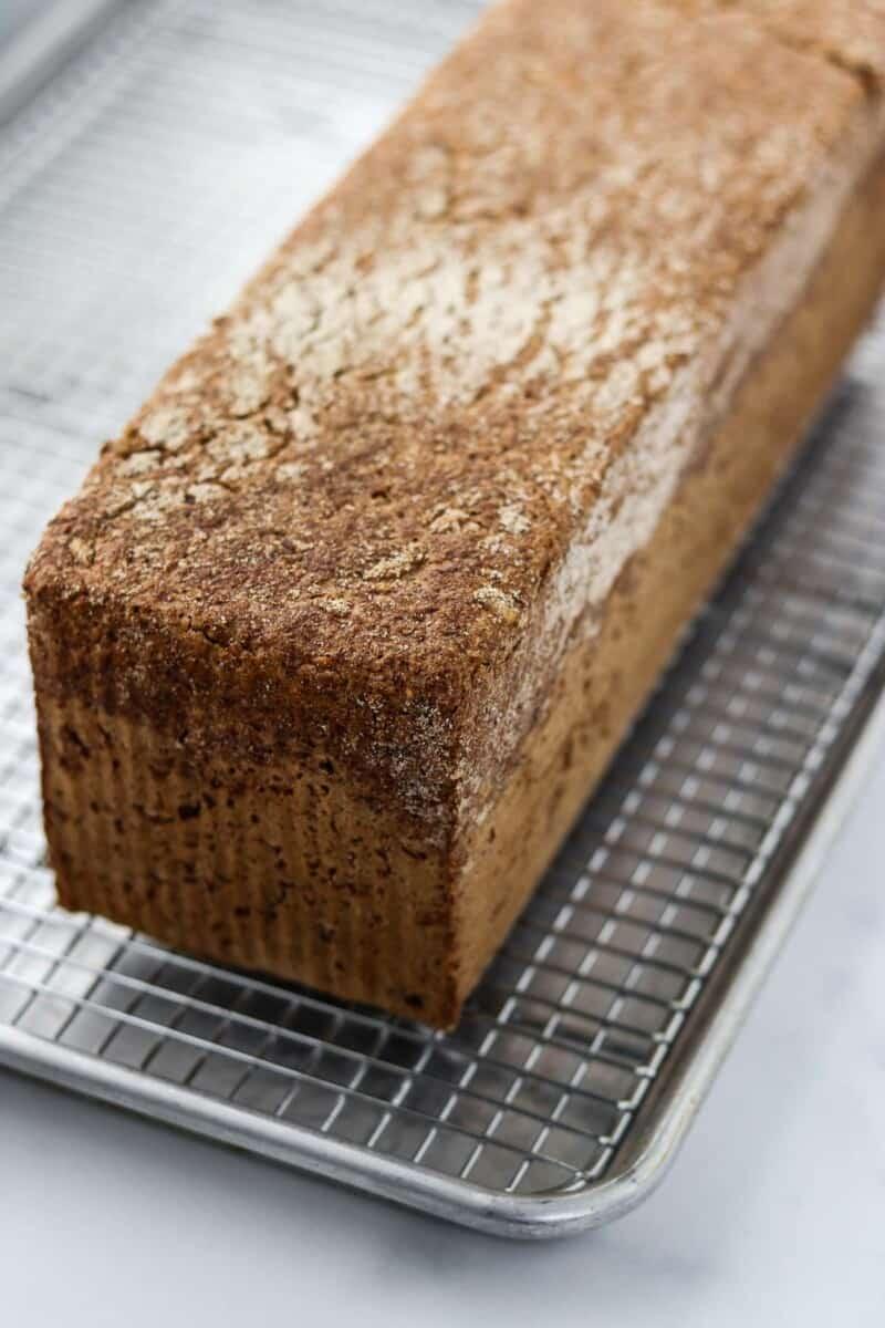 Danish rye bread on a metal cooling rack.