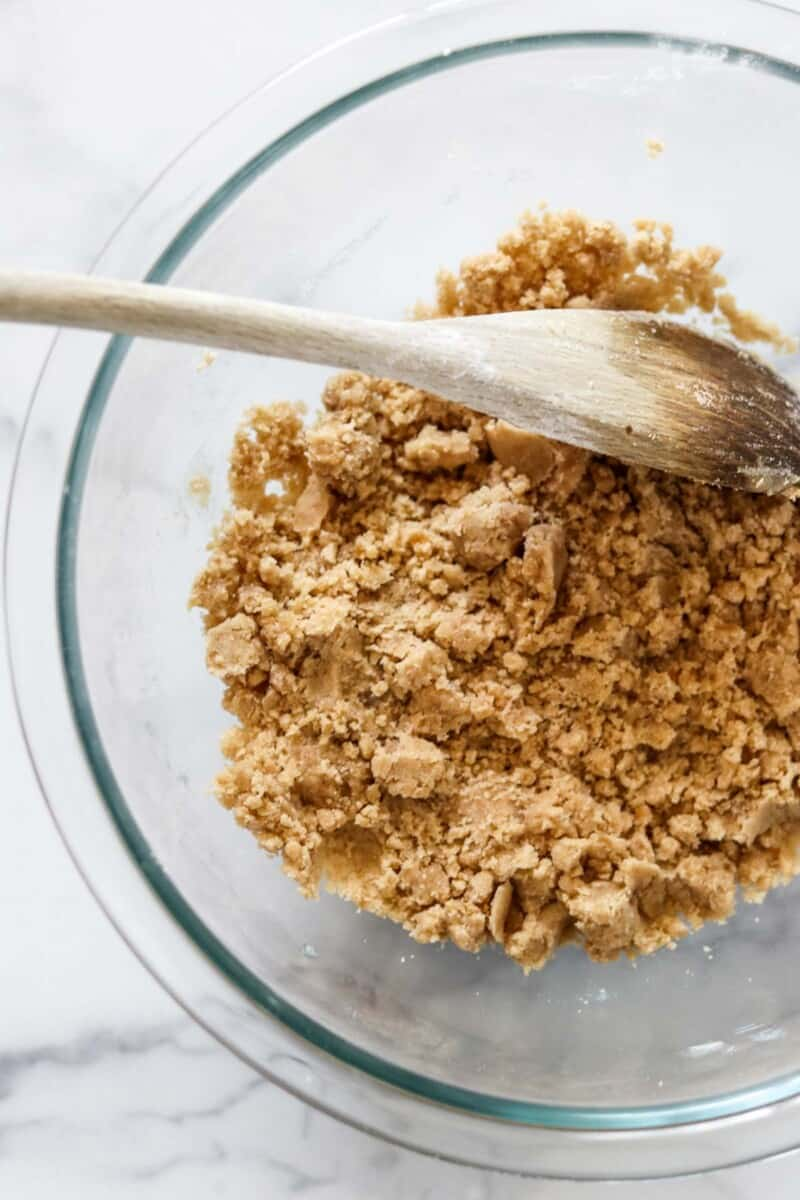 Crumb mixture in a glass bowl with a wooden spoon.