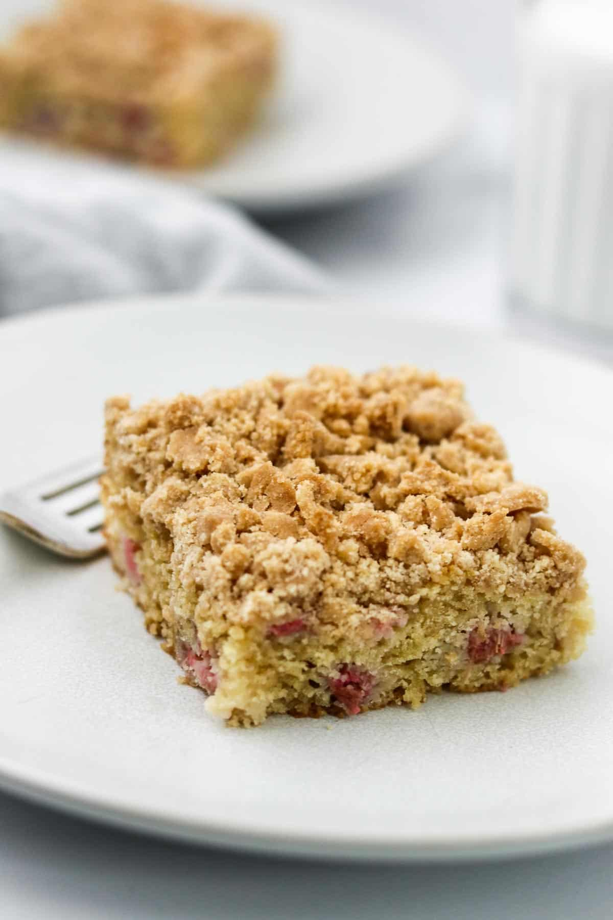 Rhubarb cake on a plate with a fork next to a glass of milk.