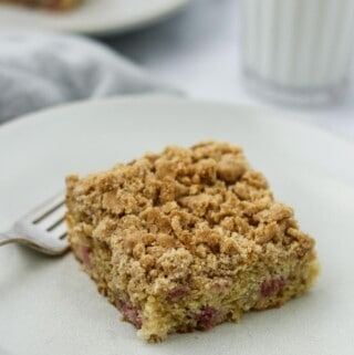 Old-Fashioned Norwegian Rhubarb Crumb Cake on a plate next to a glass of milk.