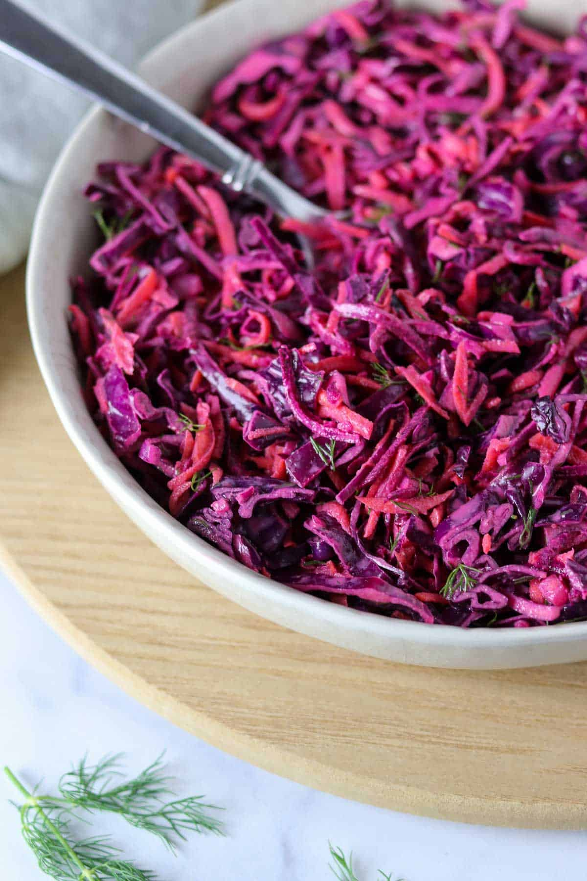 Red Cabbage Slaw in a bowl with a spoon on a wooden surface.