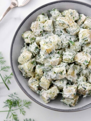 Creamy Herbed Potato Salad in a bowl next to a spoon and dill sprigs.