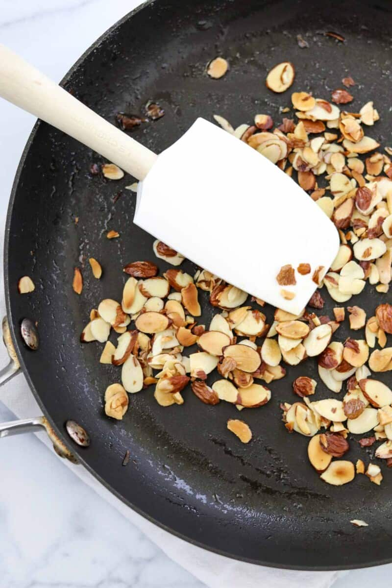 Toasted almonds in a skillet with a white rubber spatula.