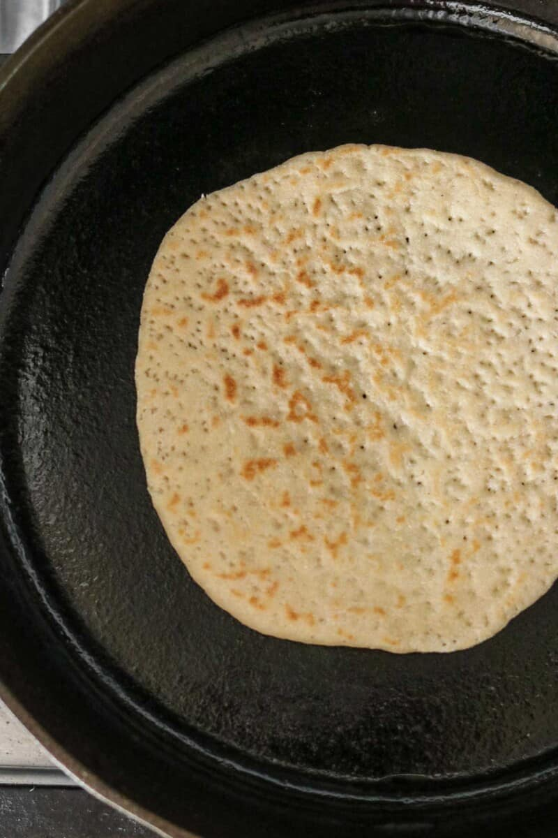 Flatbread cooking in a cast iron skillet.