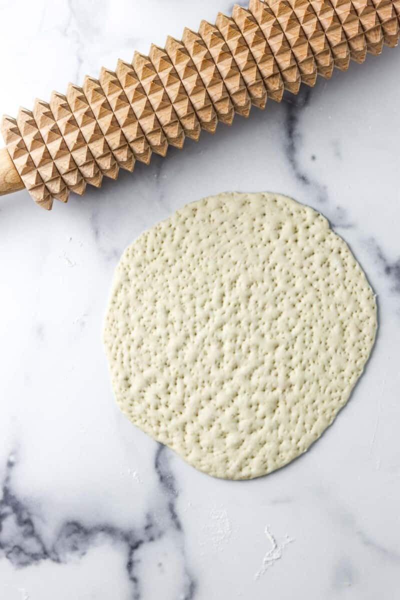 Flatbread dough rolled out on a marble counter with a spiked rolling pin.