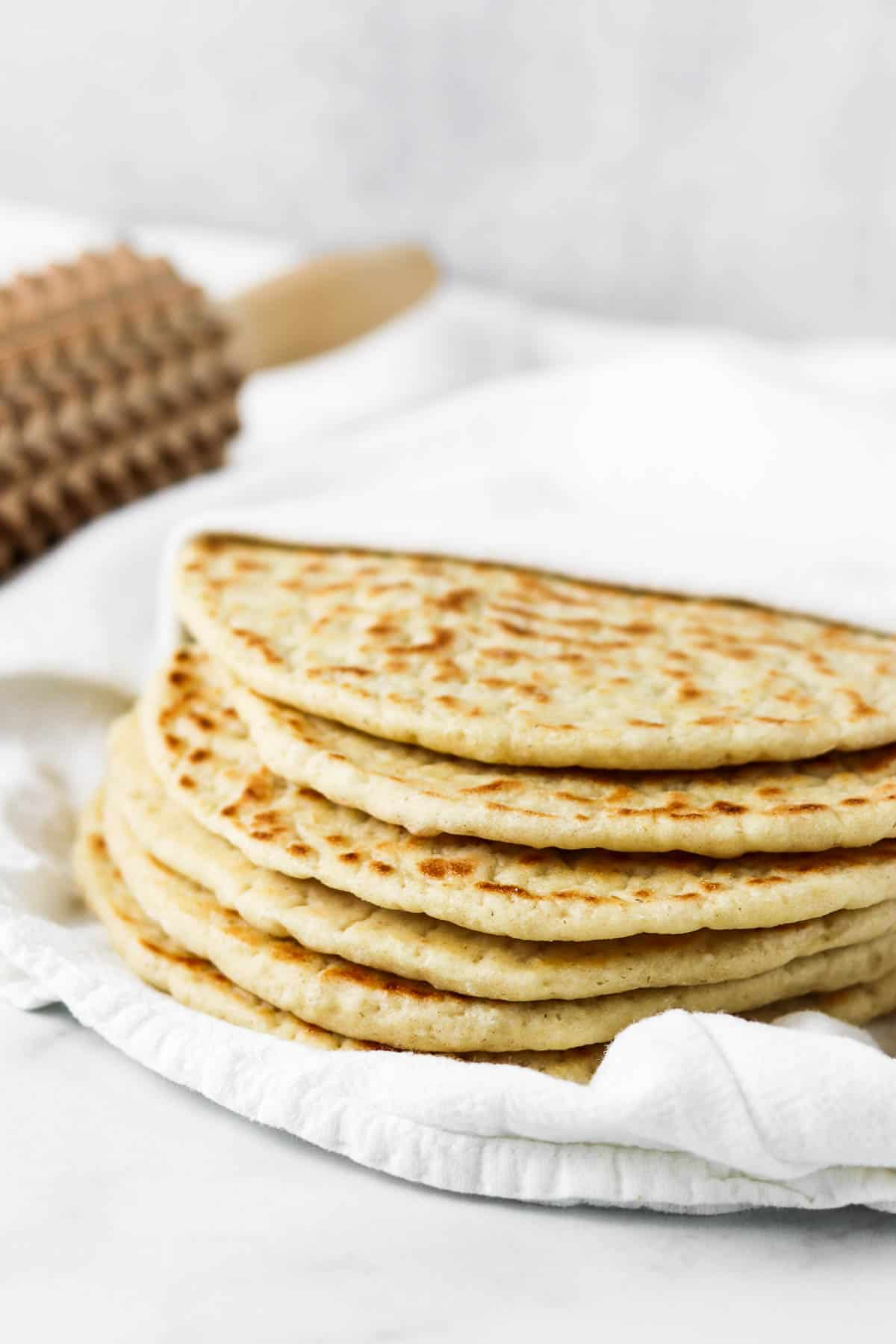 Stack of flatbreads on a towel.