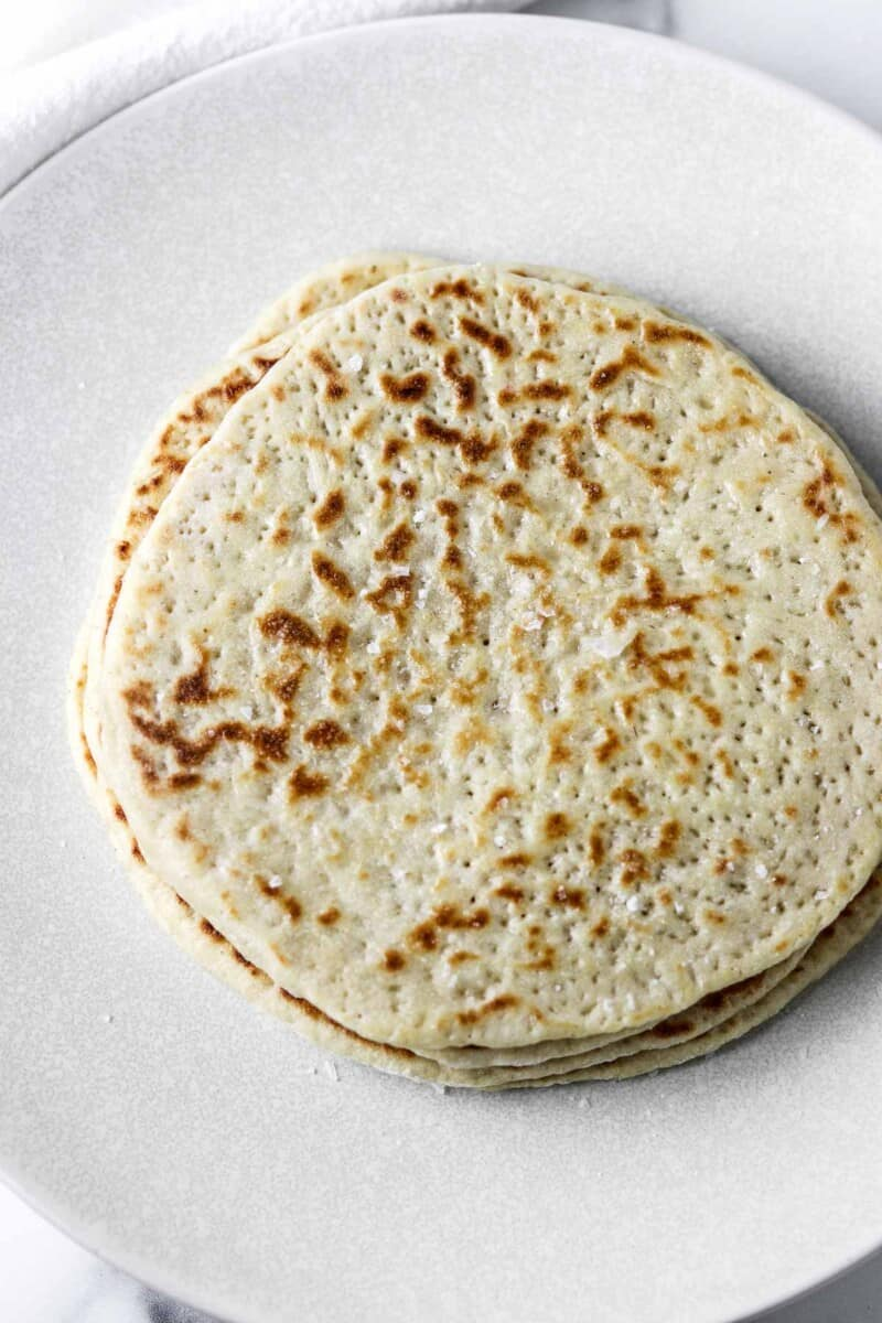 Stack of flatbreads on a white plate.