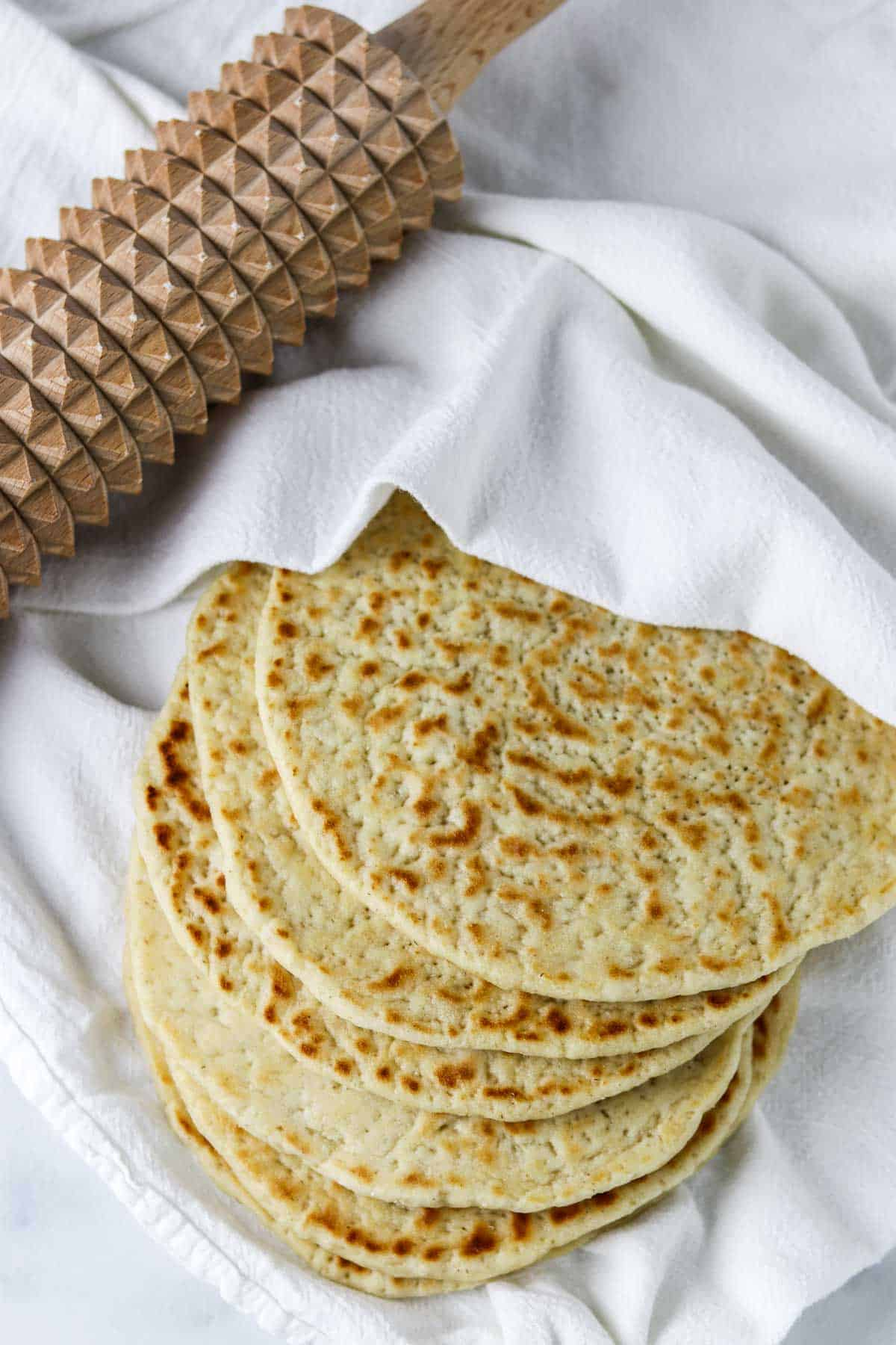 Flatbreads on a towel next to a spiked rolling pin.