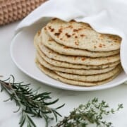 Stack of flatbreads on a plate next to herbs and a spiked rolling pin.