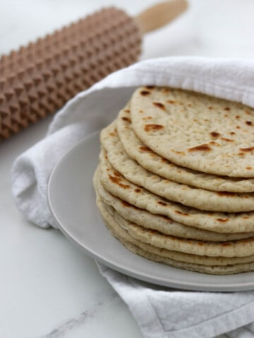 Soft Swedish Flatbreads on a plate next to a towel and a spiky rolling pin.