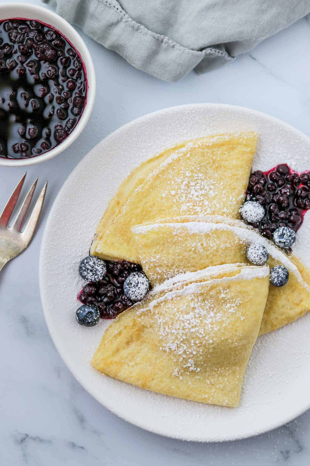 Swedish pancakes topped with blueberries and powdered sugar.
