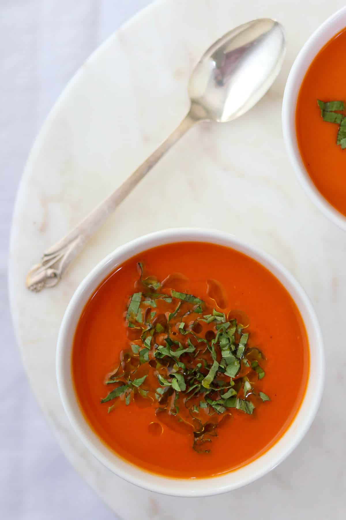 Two bowls of tomato red pepper soup topped with basil